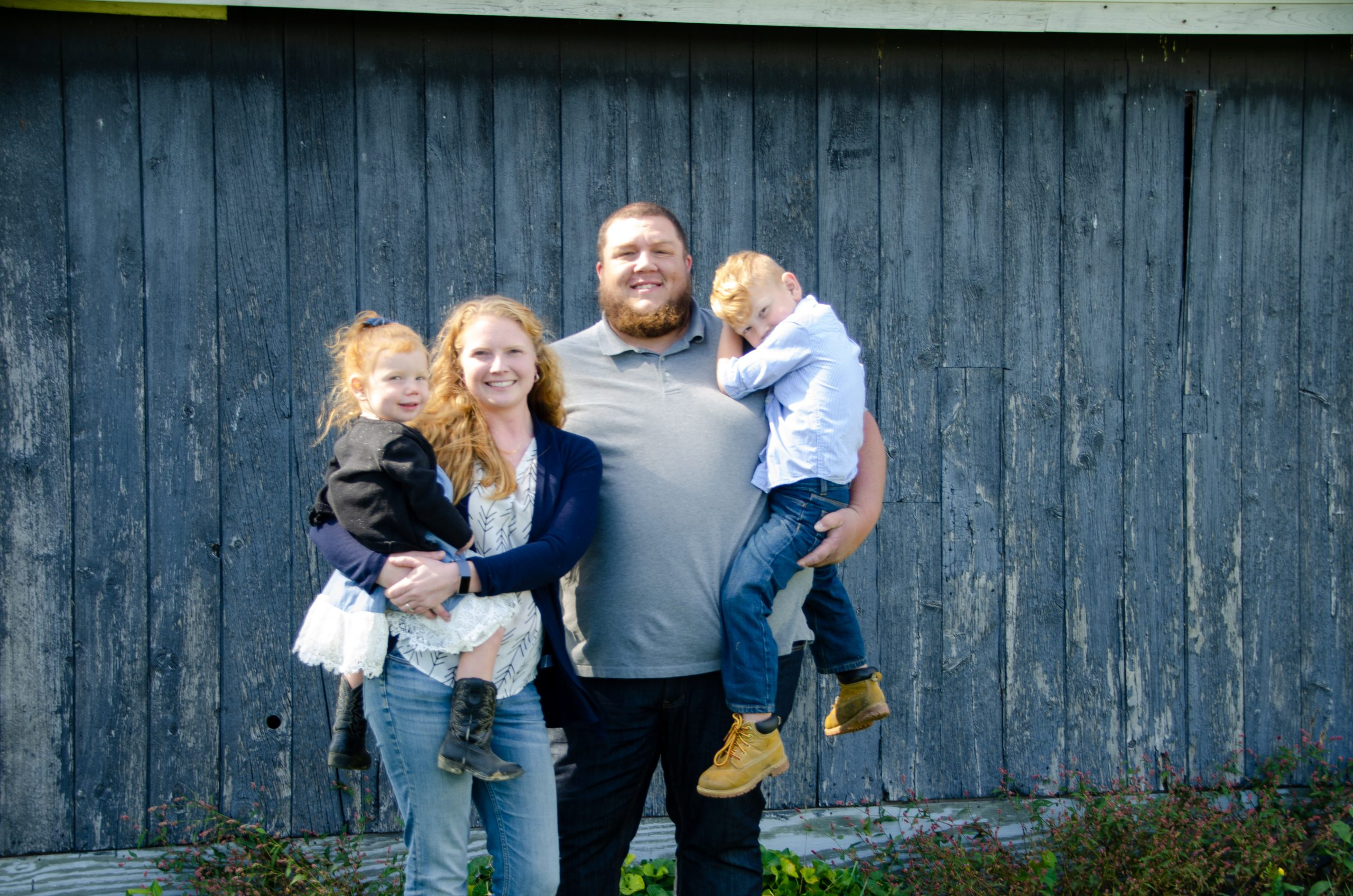 The Rupprecht Family in front of a grey barn wall.