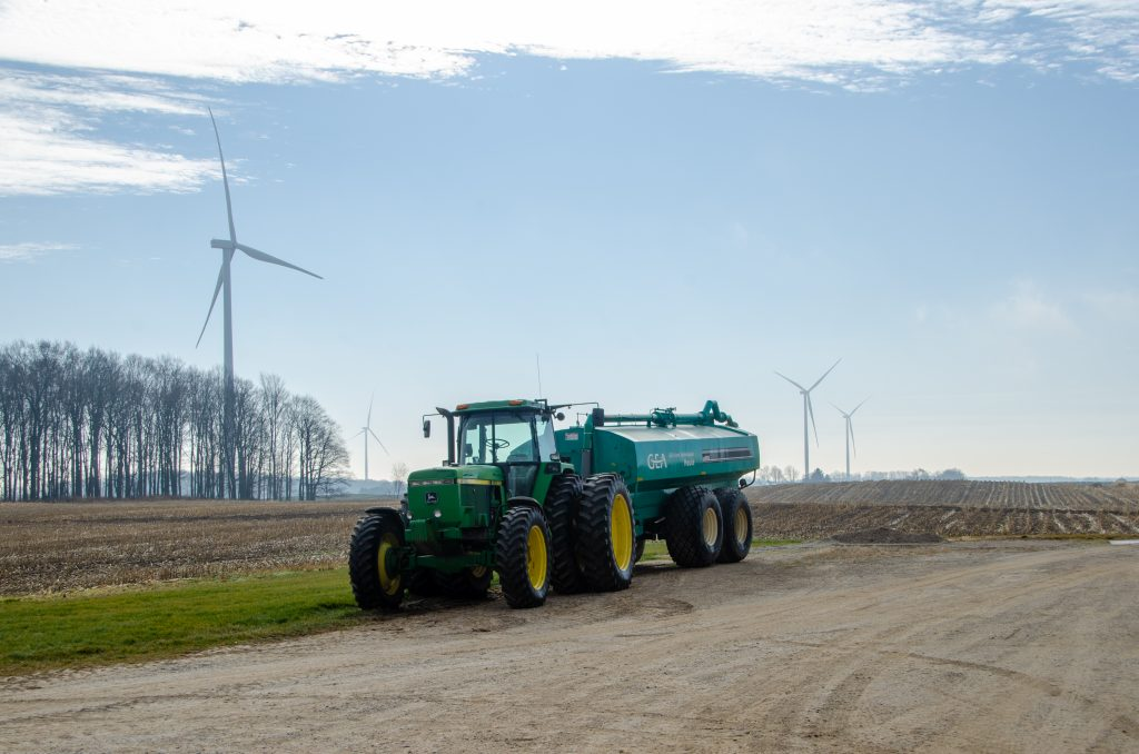 Tractor parked in front of windmill on Gross Farms Registered Holsteins, MMPA 2020 Quality Award Winners..